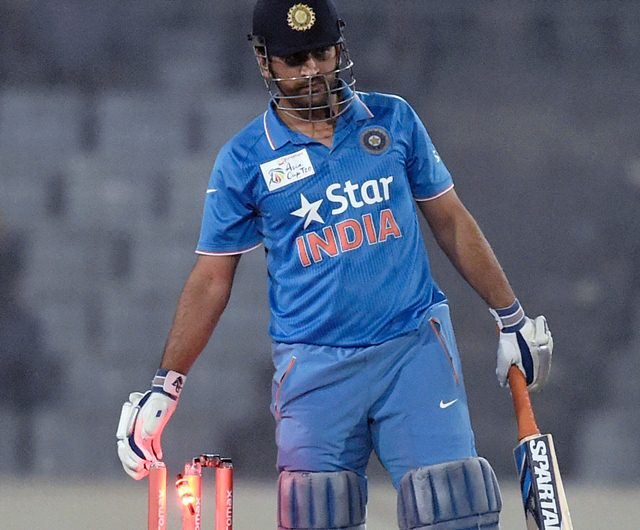Mahendra Singh Dhoni removes one of the two bails from the stumps India