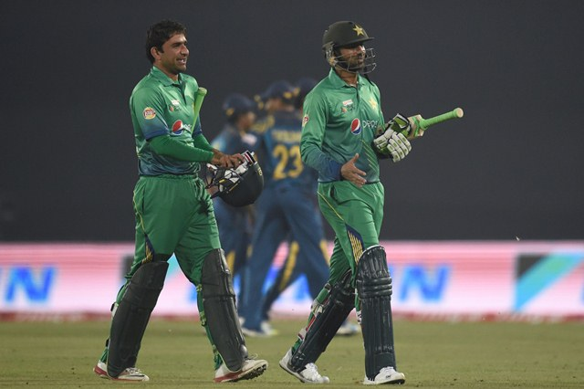 shoaib Malik and his teammate Iftikhar Ahmed walk off the field