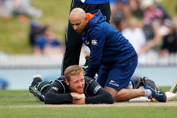 Medics check the injury to Martin Guptill of New Zealand