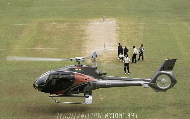 A helicopter tries to dry the pitch